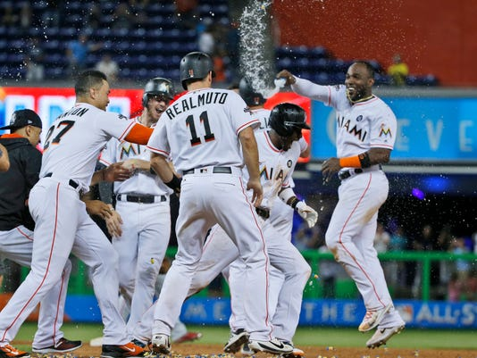 Miami Marlins' Dee Gordon, second from right, is mobbed by teammates after hitting a single to score J.T. Realmuto in the 10th inning to defeat the Philadelphia Phillies 6-5 in a baseball game, Monday, July 17, 2017, in Miami. (AP Photo/Wilfredo Lee)