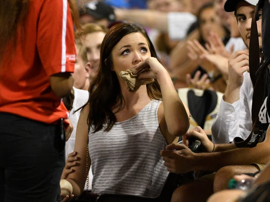 A fan wipes her lip after she was hit on the mouth by a foul ball hit by Kansas City Royals' Brandon Moss during the third inning of the Royals' baseball game against the Chicago White Sox, Friday, Sept. 22, 2017, in Chicago. (AP Photo/David Banks)