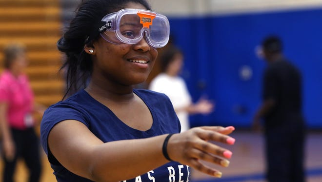 Shortridge High School sophomore Ashauntae Birdsong, wearing a Concussion Goggle that simulates blurred vision resulting from a concussion, tries to make her way across the school's gym as the Dave Duerson Athletic Safety Fund non-profit organization came to the school at 3401 N. Meridian St., Indianapolis, on Monday, Oct. 26, 2015 to heighten concussion awareness among youth. Kathy Langdon, the school's athletic director and also health and wellness facilitator at Indianapolis Public Schools, directed students in several exercises demonstrating how the goggles work. The program is intended to educate all students, not just athletes. The organization has donated more than 60 goggles for the educational program. Michael Duerson, Muncie, father of former Chicago Bear Dave Duerson, who committed suicide after suffering numerous concussions, was at the school  on Monday to promote the group's efforts.