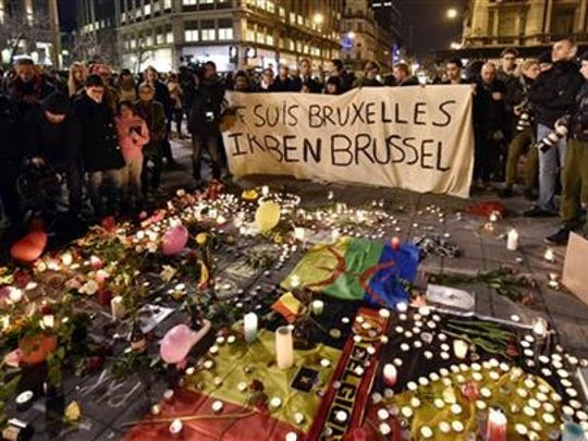 "People holding a sign saying ""I am Brussels"" at a memorial for the victims of this week's terror attack."
