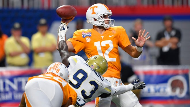 Tennessee Volunteers quarterback Quinten Dormady drops back to pass against Georgia Tech Yellow Jackets defensive lineman Antonio Simmons during the first quarter at Mercedes-Benz Stadium in Atlanta.