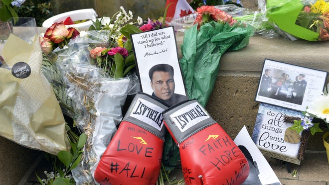 Flowers and mementos form a memorial to Muhammad Ali on Sunday at the Muhammad Ali Center.