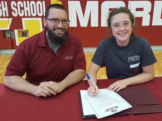 Amelia Bartels, with Aquinas College lacrosse coach Owen Blank, signs her national letter of intent to play at the Grand Rapids-based institution.