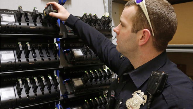 In this Feb. 2, 2015 photo, Duluth, Minn., police officer Dan Merseth demonstrates the docking procedure for police body cameras at police headquarters. Duluth initially received 84 cameras and charging bays for less than $5,000 from camera maker Taser International, but its three-year contract and licensing agreement for data storage cost about $78,000. (AP Photo/Jim Mone)