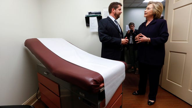 """In this May 2, 2016 file photo, Democratic presidential candidate Hillary Clinton listens to Dr. Christopher Beckett, CEO of Williamson Health and Wellness Center during a tour an exam room of the facility in Williamson, W.Va. With the hourglass running out for his administration, President Barack Obama's health care law is struggling in many parts of the country. Double-digit premium increases and exits by big-name insurers have caused some to wonder whether """"Obamacare"""" will go down as a failed experiment."""