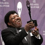 """Percy Sledge holds up a trophy back stage after being inducted into the Rock and Roll Hall of Fame. Sledge, who recorded the classic """"When a Man Loves a Woman,"""" died Tuesday."""