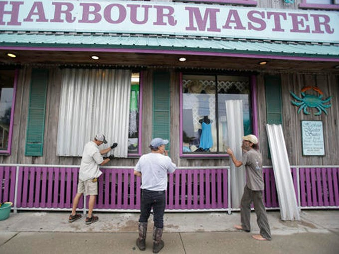 Workers install storm shutters on a store front as