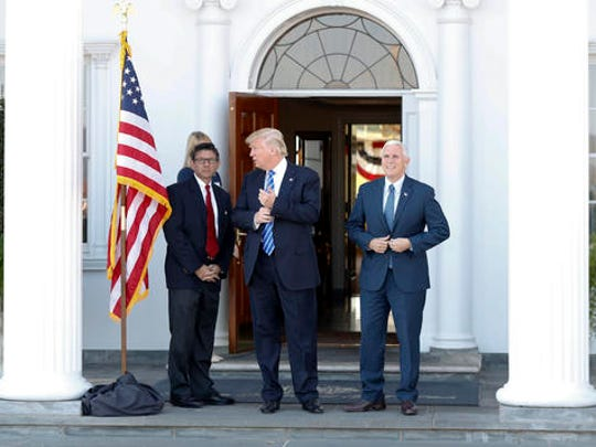 President-elect Donald Trump and Vice President-elect Mike Pence pause for photographs as they arrive at the Trump National Golf Club Bedminster clubhouse in Bedminster, N.J., Saturday, Nov. 19, 2016.