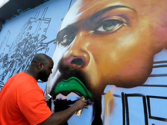 Artist Max Sansing, of Chicago, Ill., works on a mural,