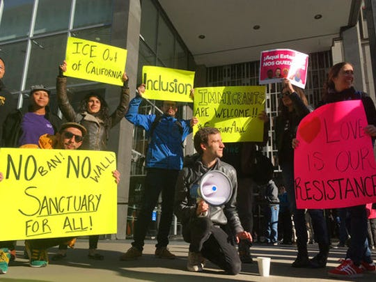 Protesters hold up signs outside a courthouse where