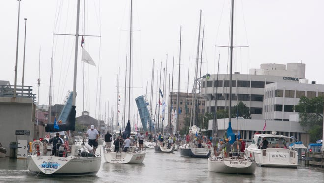 Sailboats parade out of the Black River toward the start of the Port Huron-to-Mackinac Island race  Saturday, July 22, 2017.