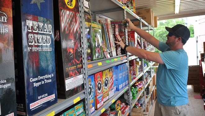 Robert Hughes stocks the shelves of the Red River Fireworks stand on FM 369 Friday afternoon in preparation for sales leading up to the Fourth of July.