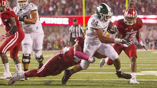 Michigan State offensive lineman Tyler Higby (70) watches as running back Gerald Holmes (24) heads for the end zone Saturday. Holmes' apparent TD was overturned by replay.