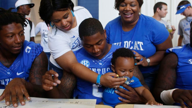 Kentucky defensive end Jason Hatcher was surrounded by family, including his sister Kelli Curry nephew Kaiden Curry and mom Donna Hatcher-Curry during football fan day at Commonwealth Stadium in Lexington, Ky. Hatcher decided to play at Kentucky to be near his family. Aug. 9, 2013