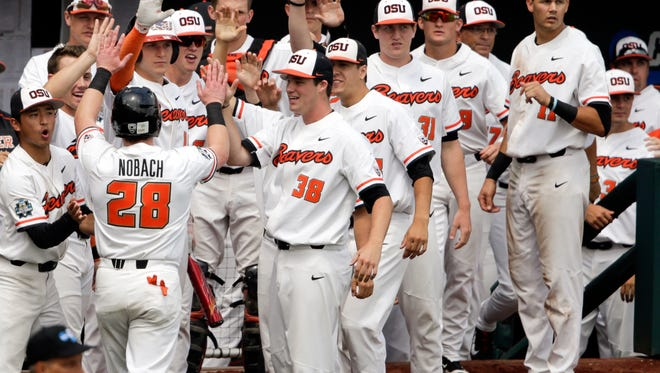 Oregon State's Kyle Nobach (28) is greeted at the dugout after he scored against Mississippi State on a one-run single by Michael Gretler in the second inning of an NCAA College World Series baseball game in Omaha, Neb., Friday, June 22, 2018.