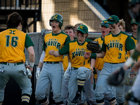 St. Xavier's Ryan Nicholson celebrates with teammates after scoring a run during the game played against Trinity on the campus of the University of Louisville in Louisville, Ky., Thursday, April 12, 2018.