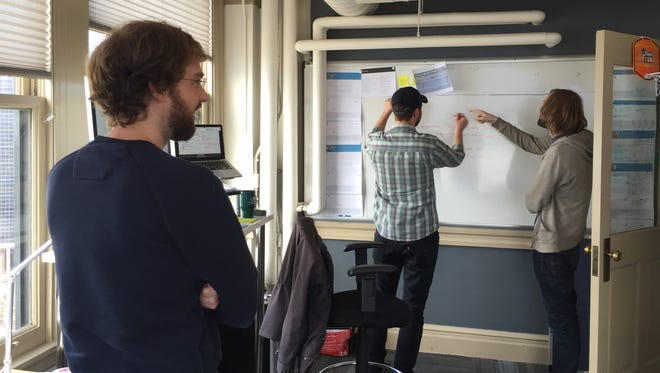 Former Ahwatukee resident Paul Gambill looks on as his coworkers brainstorm at Mentor Creative Group in Seattle.