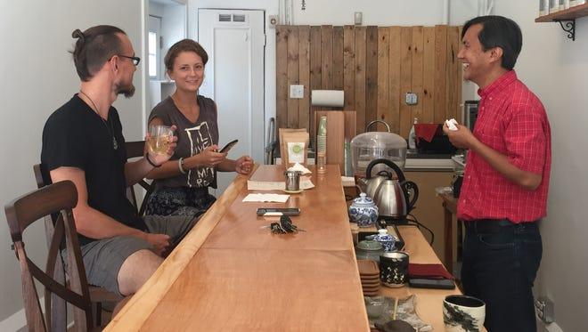 Customers Dustin Burns, 32, and Christina Vysochan, 23, of Rochester, talk with Niraj Lama, owner of Leaf Tea Bar.