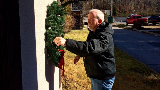 """Greg Bennett, pastor of the Gatlinburg Presbyterian Church, re-hangs a Christmas wreath Friday, Dec. 2, 2016 that was blown away by the wind during Monday's wildfires. """"We could use some Christmas spirit,"""" Bennett said as he fixed up the outside of the building."""