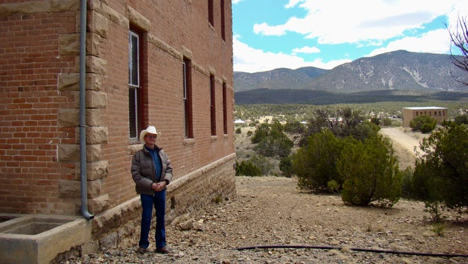 Gary Hightower is shown standing by the White Oaks Schoolhouse museum. Built in 1895, it is thought to be a fine example of a 4-room in New Mexico. The eastern-influenced school building is owned and maintained by the White Oaks Historical Association.