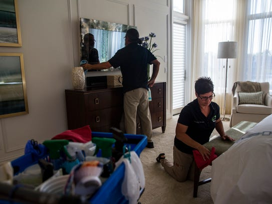Gigi and Fred Bachmann clean the bedroom of a client's