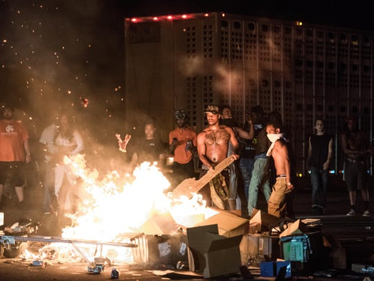 People put cargo from tractor trailers on a fire during protests.