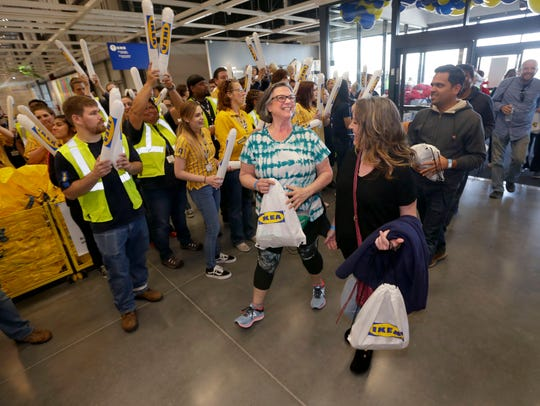 Patricia Gieringer (left), of Menomonee Falls, Wisconsin, smiles as she enters into IKEA as employees cheer. She was with her friend, Shanna Bremer (right), also of Menomonee Falls.