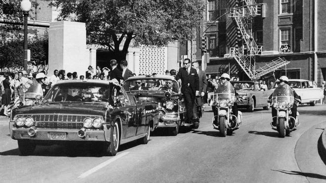 FILE - In this Friday, Nov. 22, 1963 file photo, seen through the foreground convertible's windshield, President John F. Kennedy's hand reaches toward his head within seconds of being fatally shot as first lady Jacqueline Kennedy holds his forearm as the motorcade proceeds along Elm Street past the Texas School Book Depository in Dallas.