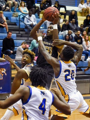 Treasure Coast's Calvin King (21) goes for the layup as he's mobbed by Martin County defenders Friday, Dec. 29, 2017, during the Don Wallen Holiday Tournament championship game at Martin County High School in Stuart.