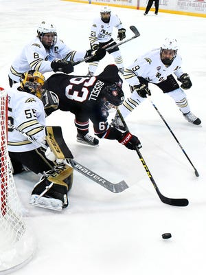 St. Cloud State's Patrick Russell is surrounded as he tries to slip the puck past Western Michigan goalie Lucas Hafner during the first period Friday at the Herb Brooks National Hockey Center.