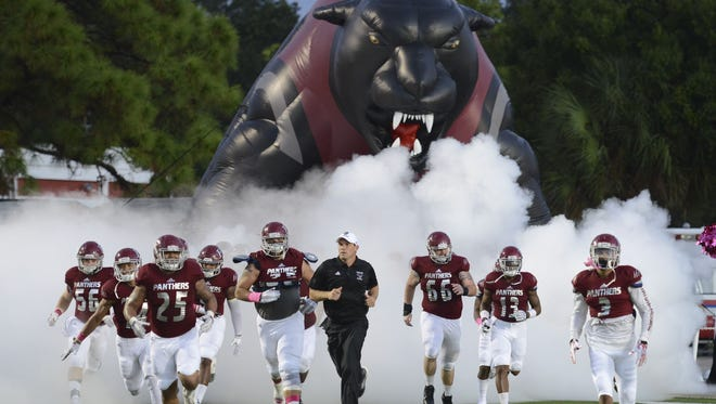 Florida Tech's football players charge the field amid fog and a big blowup panther.