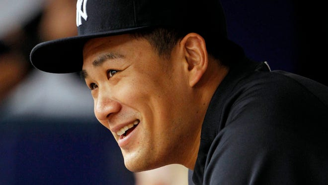 New York Yankees pitcher Masahiro Tanaka (19) smiles in the dugout against the Tampa Bay Rays at Tropicana Field.