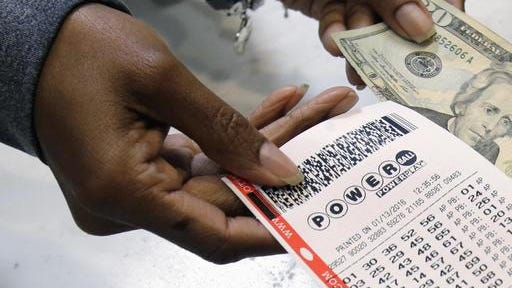 In this Jan. 13 file photo, a clerk hands over a Powerball ticket for cash at Tower City Lottery Stop in Cleveland. The Associated Press has learned that the group that runs Powerball approved, then backed off, changes that would have given ticket buyers more bang for their two bucks than the game redesign implemented last year. In October, Powerball managers changed the game's matrix in a bid to build bigger jackpots to revive lagging player interest and ticket sales.