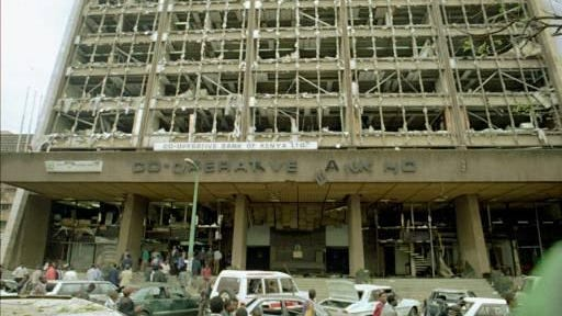 People walk past the bomb-damaged Co-Operative Bank House following an explosion in Nairobi on Aug. 7, 1998. The blast killed 224, and hundreds were injured after a bomb exploded outside the U.S. embassy. U.S. ambassador to Kenya, Prudence Bushnell, was cut on the lip and helped from the nearby Cooperative Bank House, where she had just given a news conference, embassy spokesman Bill Barr said.