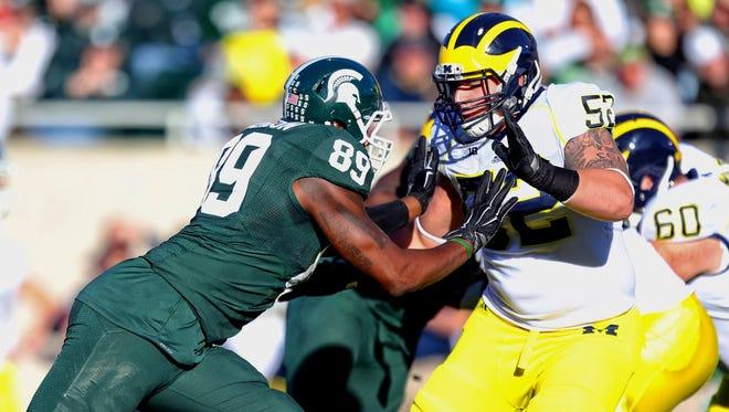 Michigan State defensive end Shilique Calhoun, left, rushes Michigan offensive lineman Mason Cole at Spartan Stadium.