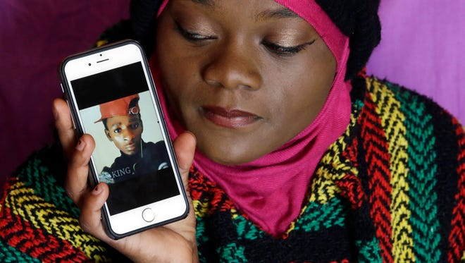 Abdi Mohamed's cousin Muslima Weledi holds a photograph of him during a interview Thursday, March 3, 2016, Salt Lake City. Mohamed, a 17-year-old Somali refugee critically wounded in a high-profile police shooting in Utah fled to the U.S. from a refugee camp where food was scare, scorpions scurried everywhere and a toilet was a hole in the ground. Mohamed's family settled in Salt Lake City, hoping for a better life.