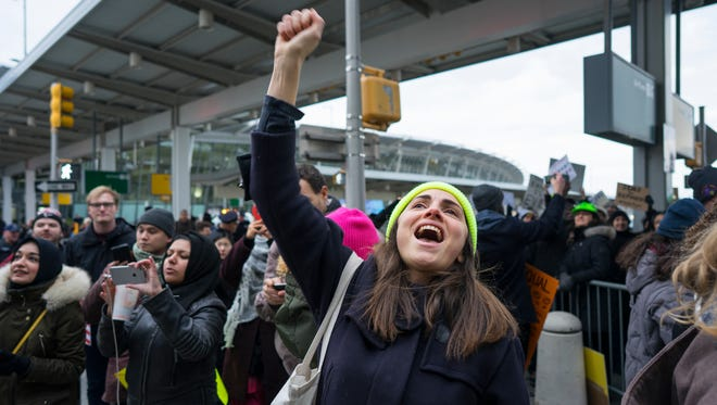 A protester raises her fist and shouts as she joins others at John F. Kennedy International Airport in New York, on Jan. 28, 2017 after two Iraqi refugees were detained while trying to enter the country.