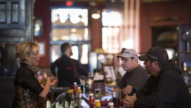 Martha Mekeel (left) talks with customers, Bob Johnson (right) and Larry Hadley (center), November 6, 2017, at the Palace Saloon and Restaurant 120 S. Montezuma Street, Prescott, Arizona.