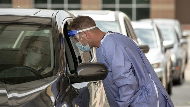 Registered nurse Keith M. prepares to take a sample from Jennifer Covert at a drive-through COVID-19 test site at Austin Emergency Center on South Lamar Boulevard on Wednesday July 8, 2020.