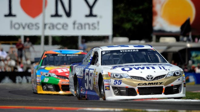 Brian Vickers leads Kyle Busch during last year's Cheez-It 355 at The Glen at Watkins Glen International, with a sign indicating the track's relationship with New York state in the background.