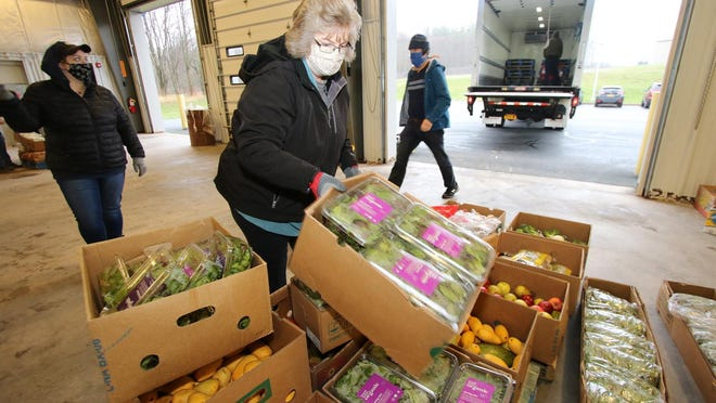 Volunteer Jenna Sayers on Thursday helps load palletsof food for distribution to various food pantries and community groups in Sullivan County.