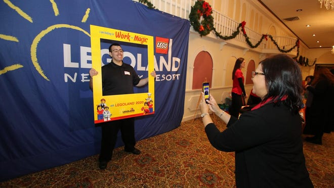 Legoland employee Rosa Gutierrez takes a picture of Jiovanni Moreno at the job fair Saturday in Middletown. Moreno received a job offer to work in the food and beverage department.