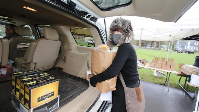 Volunteer Laura Silverman puts an order into the back of a car at the Barryville Farmers'Market. Customers order online Tuesday and pick up Saturday in the parking lot at the Barryville United Methodist Church, where the summer market is held, without getting out of their cars.