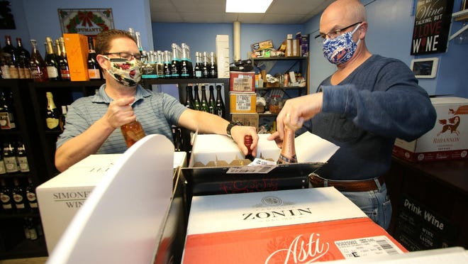 Goshen Plaza Liquors owner Jamie Blanchette, left, and general manager Marty Knapp get a delivery ready.