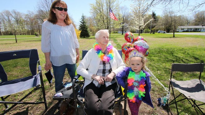 Betty Stokes, seated, turned 90 on Saturday. Stoke's daughter, Susan Tillson, left, and great-granddaughter, Madison Decker, 3, looked at a caravan of cars, trucks, firetrucks, town personnel, police cars, family members, and friends as they passed and waved to her in front of the MarbletownElementary School.