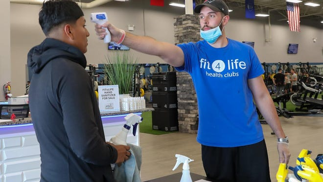Fit4Life manager, Eric Vandreuil, takes the temperature of a member before entering the fitness center Monday afternoon.