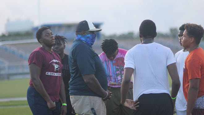 Northside assistant football coach John Davis talks to a small group of players during a recent summer workout.