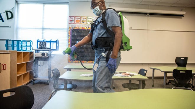 A custodian cleans a classroom at Akin Elementary in Leander on Thursday. The school has been preparing for possible return of students by cleaning and disinfecting classrooms to help prevent the spread of the coronavirus.