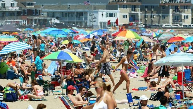 A large crowd enjoys a hot summer day at Hampton Beach.