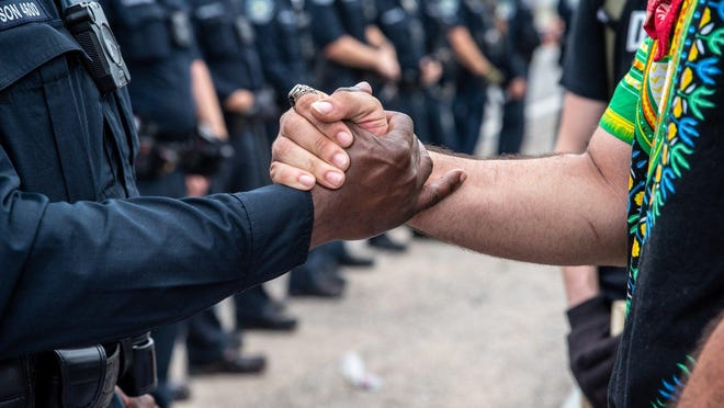Nathan Painter shakes hands Sunday with a police officer during a protest in Austin. The two had a calm discussion before exchanging information and shaking hands.